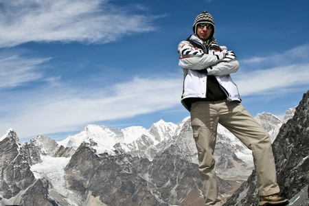 Climber standing on the top of Kongma La pass with mountain range of Khumbu glacier on background