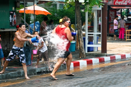 Chiang Mai, Thailand - April 13, 2010 - Thai guy throws water at tourist on April 13, 2010 in Chiang Mai, Thailand. Celebration of Thai New Year (Songkran water festival) in 2010.
