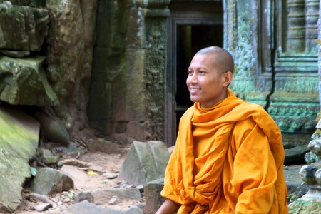 Siem Reap, Cambodia - December 1, 2010: A monk sits on ruins of the Ta Phrom temple at Angkor Wat. Publikacyjne