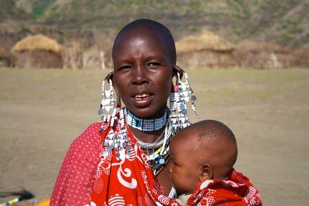 sick kid: Lago Natron, Tanzania - el 23 de febrero de 2011: Mujer masai no identificado alimentar a su hijo enfermo.