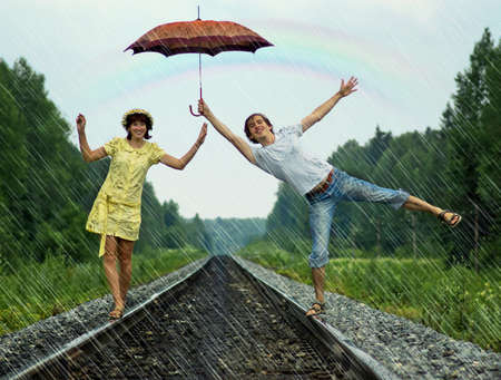 ferrocarril: Pareja joven bajo la lluvia sobre las vías del tren Foto de archivo