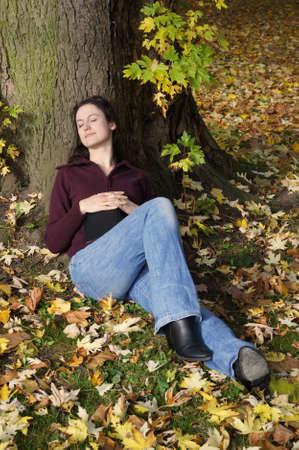 under tree: woman sleeping under tree                Stock Photo