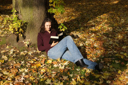 woman reading a book in autumn scene                photo