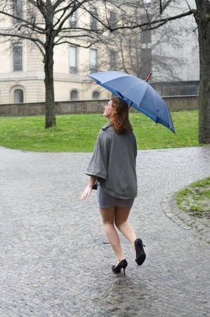 young woman running through the rain