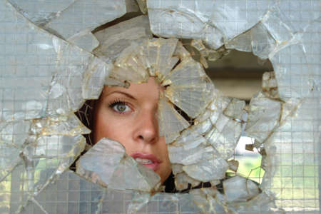 woman looking through smashed window                                Stock Photo