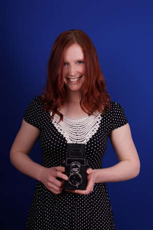 smiling woman in polka dot dress with old TLR camera photo