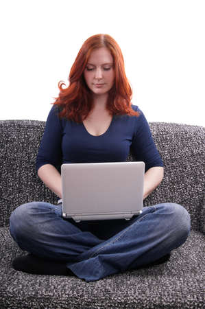 woman sitting on couch with netbook