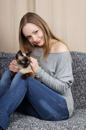happy young woman with siamese cat photo