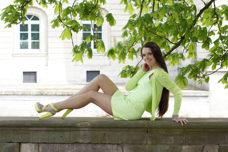 smiling woman sitting on stone wall under a tree