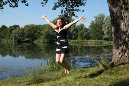 young woman jumping for joy at a lakeside photo