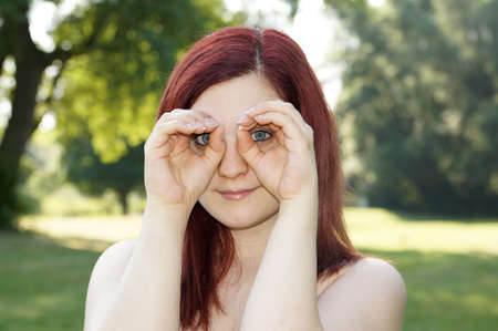 young woman imitating binoculars with her fingers around her eyes photo
