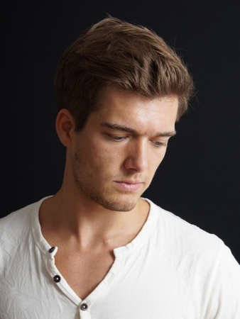 stubble: introverted young man looking down Stock Photo