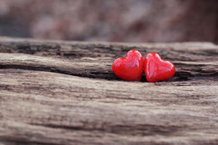 2 shiny red ceramic hearts on weathered wooden background photo