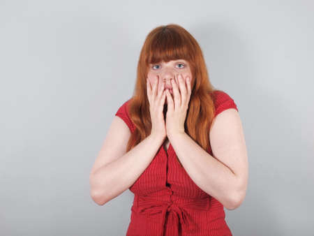 shocked young woman covering her mouth with her hands photo