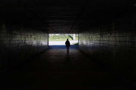 silhouette of a person walking through a dark underpass symbolizing light at the end of the tunnel photo