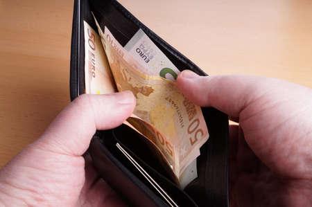 dinero euros: apertura hombre billetera de cuero negro llena de billetes de banco en euros