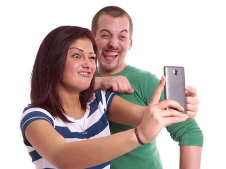 スマート フォンとのセルフ ポートレートを取っている間愚かな顔を作る 写真素材