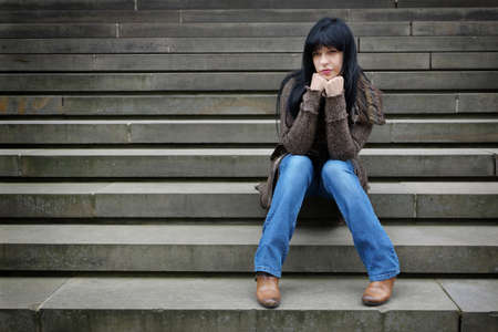 lonely woman sitting on steps outside