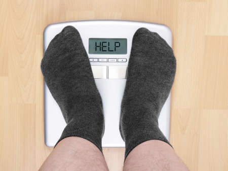 overweight man on personal scales 스톡 콘텐츠