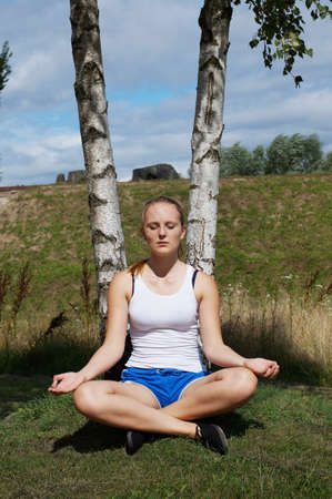 young woman meditating while sitting cross-legged in lotus position