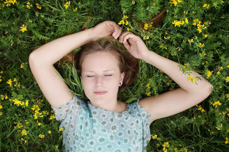 catnap: portrait of young woman sleeping in a field of flowers Stock Photo