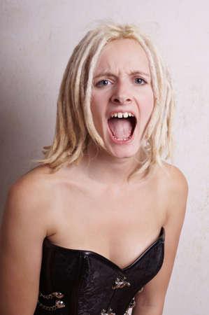femme bouche ouverte: et les cris jeune femme avec des dreadlocks blondes dans une rage