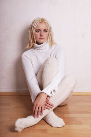 sullen: lonely woman wearing turtleneck sweater and overknee socks sitiing on floor leaning against wall