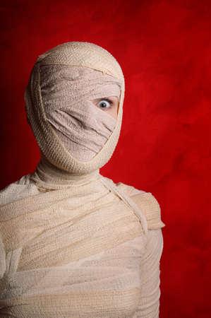 wide-eyed female mummy covered in bandages