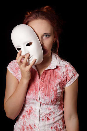 unmask: female zombie with halloween mask and bloody shirt