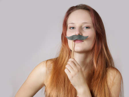 transgender: young woman holding a fake moustache on a stick to her face