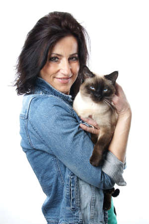 woman in her forties holding siamese cat
