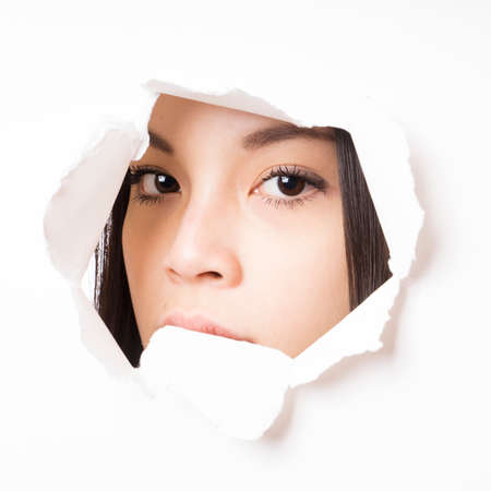 furtively: young asian woman peeking through hole torn in paper wall