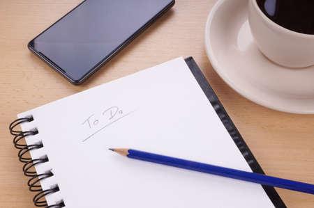 A-hacer la lista con libreta, lápiz, teléfono móvil y una taza de café en la mesa Foto de archivo - 33582231