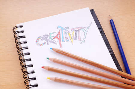 colored paper: writing pad with the word creativity drawn with colored pencils