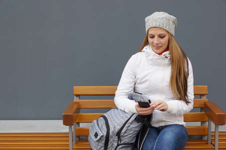 young woman sitting on bench checking her phone while waiting photo