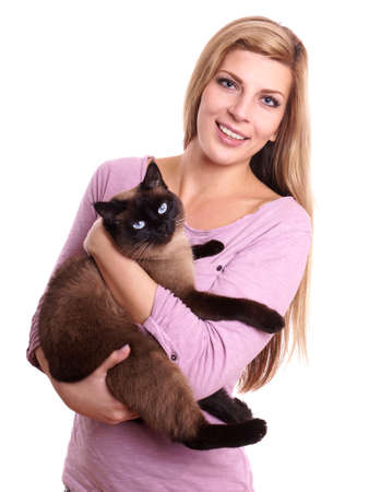 young woman holding siamese cat in her arms