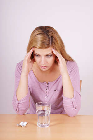 young woman suffering from headache with glass of water and tablets photo