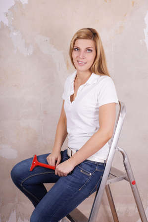 woman knife: young woman sitting on ladder during refurbishment