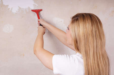 white wallpaper: young woman is scraping off old wallpaper