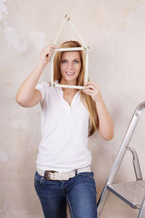 yardstick: young woman made house shape from yardstick