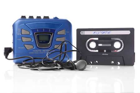 old-fashioned music cassette and portable mp3 player with earphones