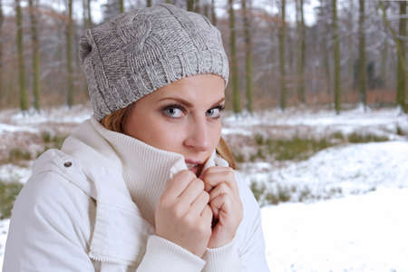 young woman wearing woolen hat and winter jacket is freezing photo