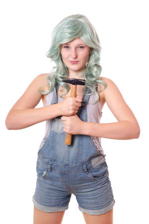 dungarees: emancipated young woman with green hair and jeans dungarees holding hammer