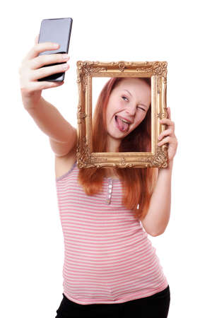young woman taking a silly selfie with picture frame with camera phone photo