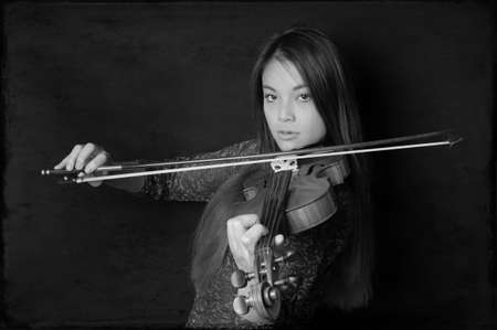 young asian woman playing violin in black and white photo