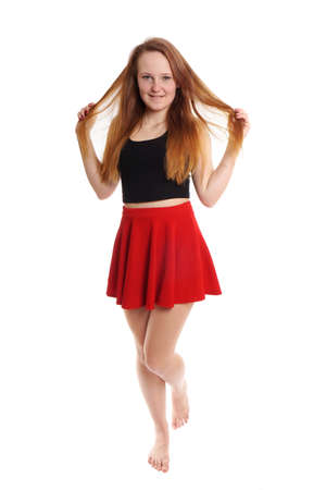 cheeky: full body shot of young woman wearing red mini skirt playing with hair