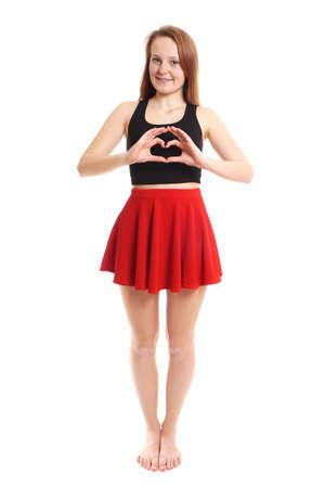 minifalda: longitud completa de la mujer joven haciendo en forma de corazón con sus manos