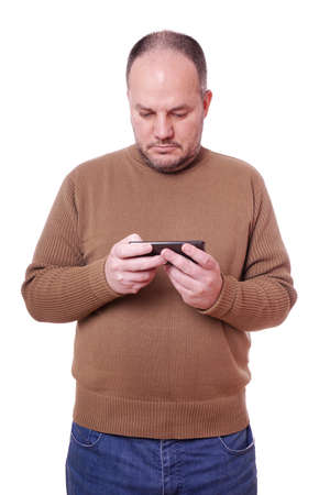 man looking down: middle aged man looking down at his mobile smart phone