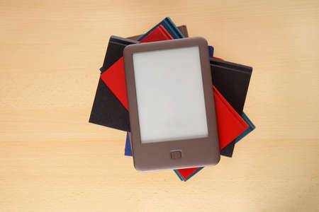 modern ebook reader on top of pile of old books photo