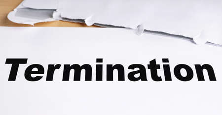 termination: termination letter with opened envelope on desk Stock Photo